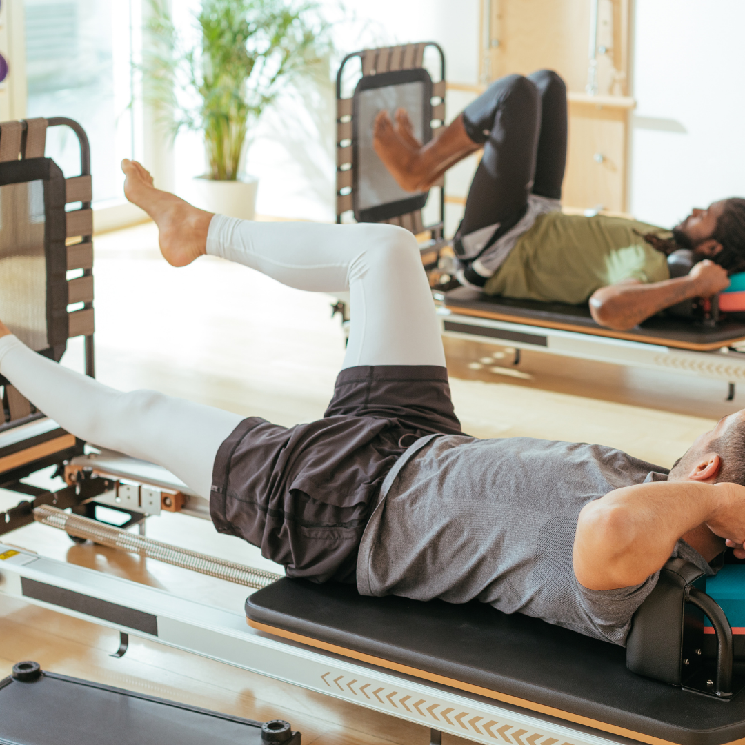 Two men doing jump an dfootwork pilates exercises on a pilates reformer machine
